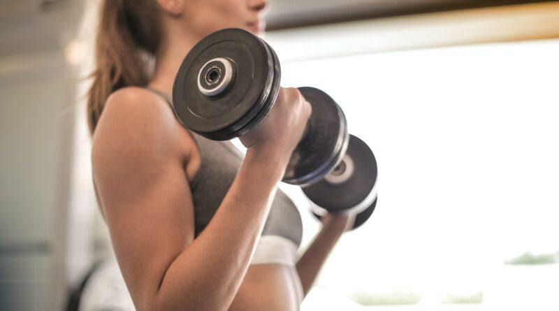 Kvinde løfter vægte i fitnesscenter